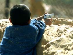 A PALESTINIAN BOY DIRECTS HIS TOY GUN TOWARDS ISRAELI SOLDIERS IN THE GAZA STRIP