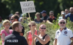 "HEIDENAU, GERMANY - AUGUST 26: An Onlooker Holds A Sign That Reads: ""Nation Traitor"" During A Visit By Angela Merkel To A Nearby Asylum Shelter."